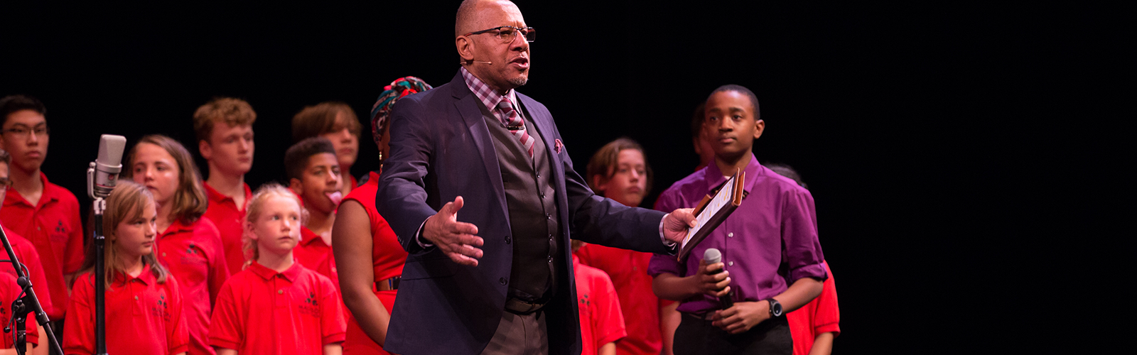 Host with children behind at the power of story event at the overture center